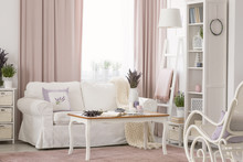 Wooden Table Next To White Couch In Pink Living Room Interior With Drapes And Plants. Real Photo