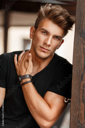 Photographie  Fresh portrait of a beautiful young model man in a black T-shirt on a street nea