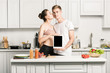girlfriend kissing boyfriend and he holding tablet with blank screen in kitchen