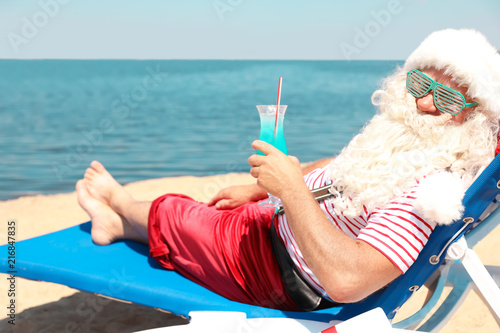 obraz PCV Authentic Santa Claus with cocktail resting on lounge chair at resort