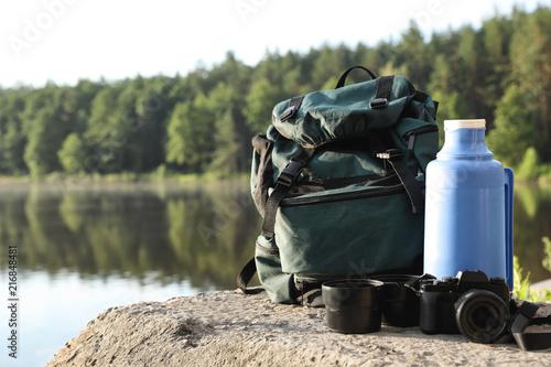 Set of camping equipment on rock near lake