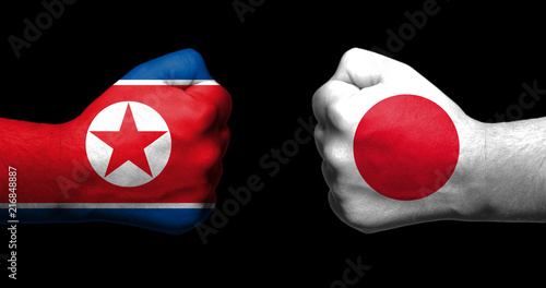 Fotografie, Obraz  Flags of Japan and North Korea painted on two clenched fists facing each other on black background/