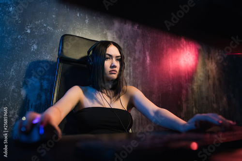 Concerned girl gamer in headphones playing network games preparing to participate in international competitions in e-sports Wallpaper Mural