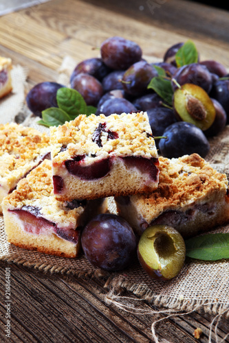 Rustic plum cake on wooden background with plums around.
