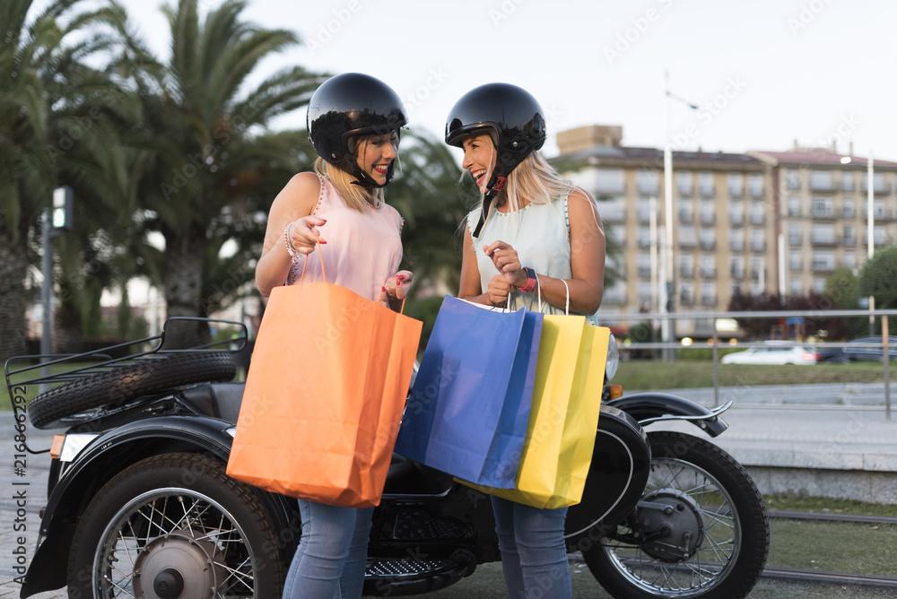 Fototapeta Dos hermananas con casco en sidecar disfrutan después de hacer la compra