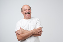 Mature Adult Man With Moustache Laughing Looking At The Camera Over White Background.