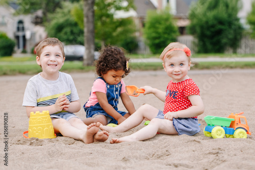 Fotografie, Obraz  Portrait of three cute Caucasian and hispanic latin toddlers babies children sitting in sandbox playing with plastic colorful toys
