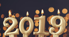 Gold New Year 2019 Celebration Candle Against Blurred Light Background. New Years Eve Festive Background