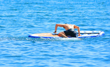 Sup Surfing Training. Stand Up Paddle. The Guy Rises To The Sap Board After Falling Into The Water...