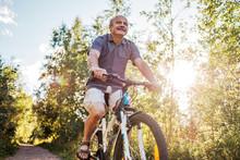 Joyful Senior Man Riding A Bike In A Park On A Beautiful Sunny Day