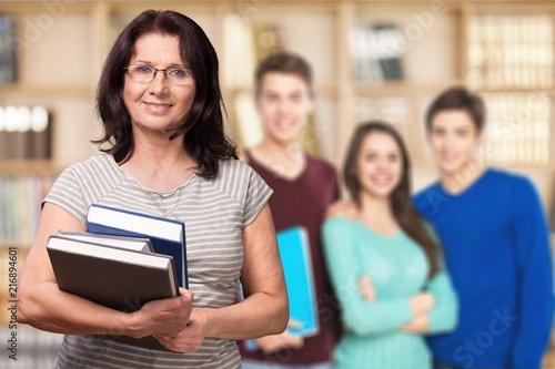 Obraz Mature woman teacher with books in library - fototapety do salonu