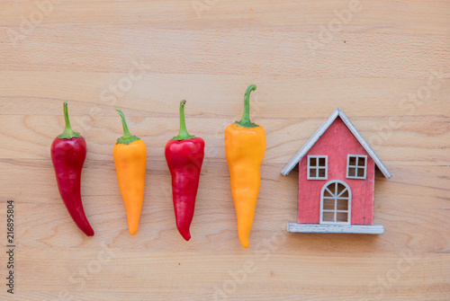 Fotobehang Kruiderij yellow and red peppers with toy house on wooden table. Above view