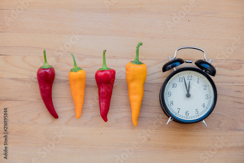 Fotobehang Kruiderij chilli peppers and alarm clock on wooden table. Above view