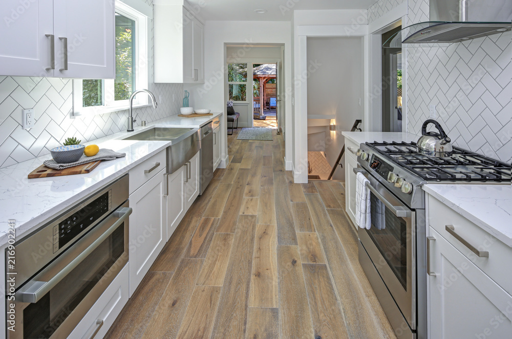 Fototapeta Remodeled kitchen with pure white cabinets.