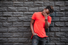 African Man Model Laughing In Red T-shirt Against Brick Wall With Facepalm