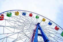 Large And Bright Ferris Wheel Against A Clear Blue Sky. Long Spokes And Multi-colored Seats. Concept Of Joy And Good Mood