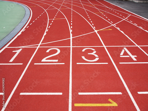 Fotografiet  Red running track with numbers at the stadium