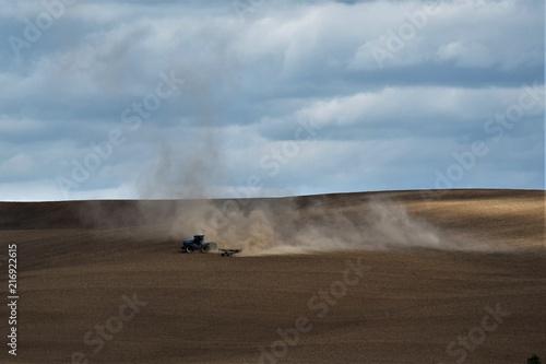 Tractor plowing dusty field 2 Wallpaper Mural