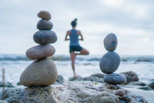 Fototapeta Beautiful girl tree pose yoga by the ocean with stacking rocks