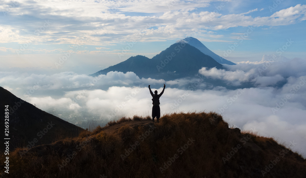 Fototapety, obrazy:  hiker person rising hand standing on walk way at volcano Batur, Bali island, Indonesia.