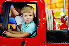Cute Teen Girl And Little Boy Ride On A Carousel In A Toy Car Arcade In Game Machine At An Amusement Park.