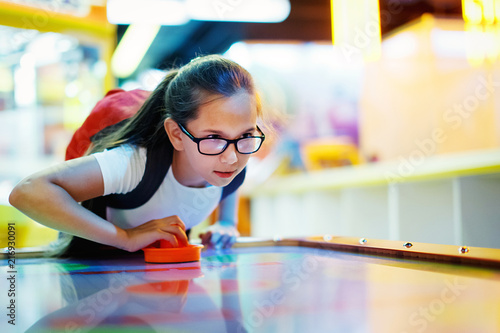 Leinwand Poster Cute teen girl plays air hockey arcade in game machine at an amusement park