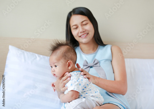 Health care after meal. Mother is belching for infant baby. Canvas-taulu