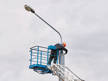 Municipal Worker Man With Helmet And Safety Protective Equipment Painting Street Lightning Pole At Height With Brush. Worker Repair Light Pole. High Elevated Cherry Picker With Worker On Floodlight
