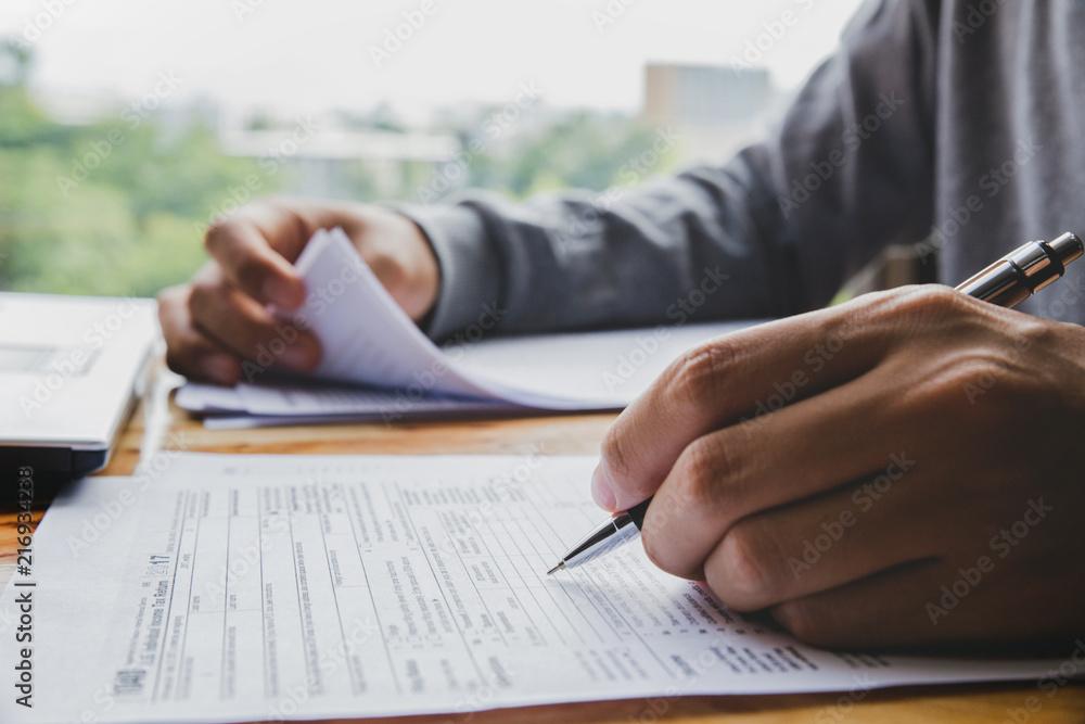 Fototapeta Closeup of man hand filling income tax forms