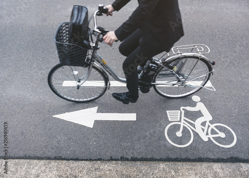 People ride bicycle on Road with bike lane sign city transportation