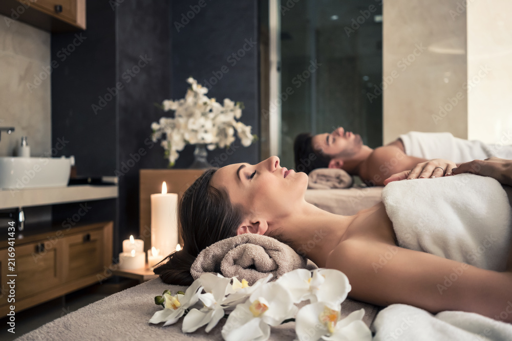 Fototapeta Young man and woman lying down on massage beds at Asian luxury spa and wellness center