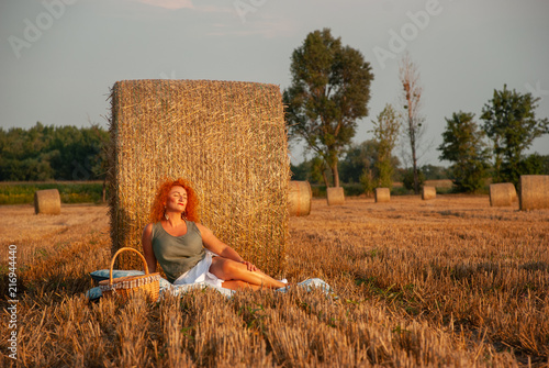 Fotografie, Obraz Red-haired woman posing on the field near a haystack