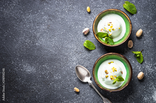 Pistachios ice cream in bowls on black stone table. Wallpaper Mural