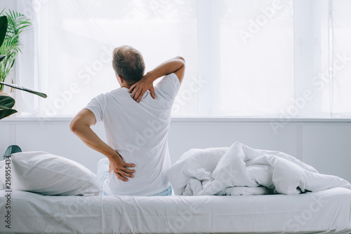 Fotografia back view of man sitting on bed and suffering from back pain