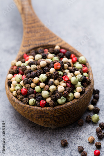 Foto op Plexiglas Aromatische Peppercorn mix in a wooden bowl on grey table.