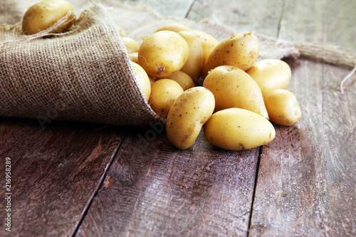 Fotografering Pile of potatoes lying on wooden boards. Fresh potato