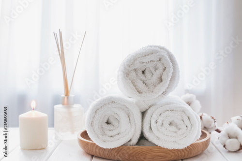 Fotobehang Spa Clean white towels on the wooden tray, candle and aroma diffuser.