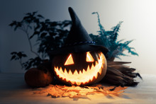 Scary Traditional Smiley Pumpkin Lantern With Corn And Dry Leaves Closeup. Halloween Holiday Background