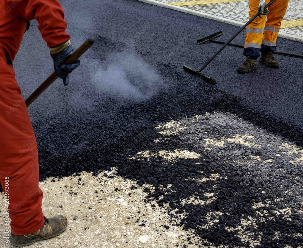 Fototapeta Worker distributes on the edge the asphalt laid out for the construction of a road