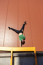 Acrobat Performing One-armed Handstand On Yellow Frame