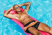 Cheerful Tattooed African American Man Sunbathing On Pink Inflatable Mattress In Swimming Pool