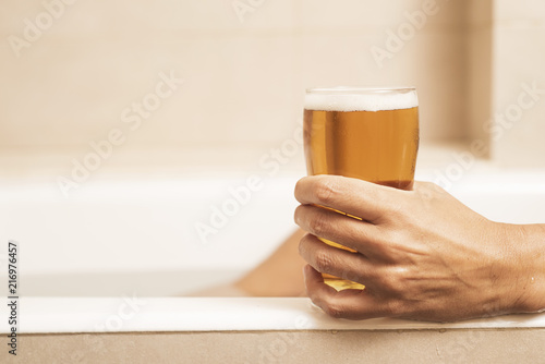 Spoed Foto op Canvas Bier / Cider young man drinking a beer on the bathtub