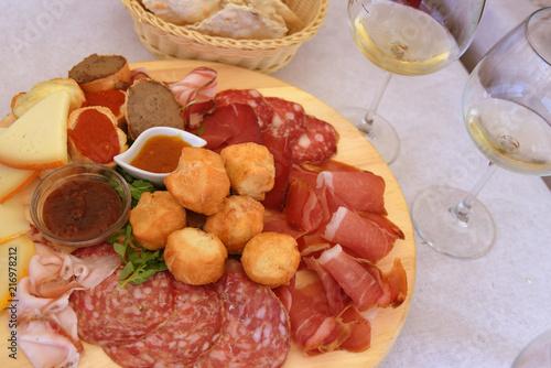Wall Murals Appetizer Leckeres toskanisches Vorspeisenbrett mit Schinken, Käse, Salami, Saucen und Coccoli sowie Brotkörbchen und Wein dazu