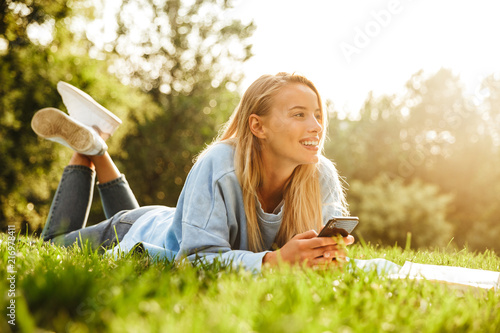 Portrait of a smiling young girl laying on a grass at the park