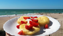 Strawberry Cheesecake  On White Plate At Beach Background