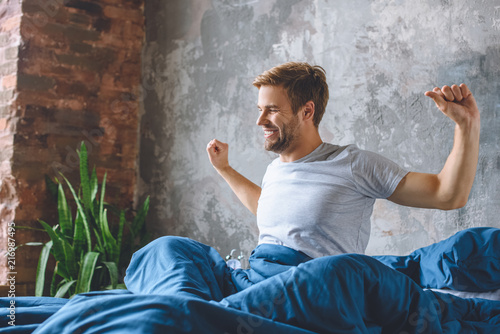 handsome young man stretching in bed during morning time at home Canvas Print