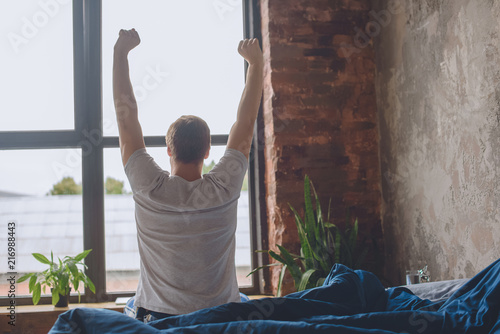 rear view of young man sitting on bed with raised arms during morning time at ho Canvas Print