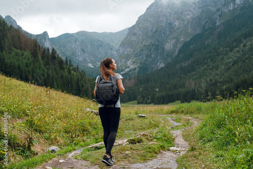 Rear shot of young brunette backpacker woman hiking on the green pathway in Tatra Mountains to Rysy peak Canvas Print
