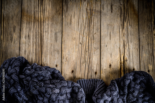 Cozy autumnal background, old rustic wooden table with a warm blanket, copy place for text