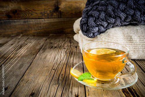 Staande foto Thee Autumn comfort and warm concept. Tea glass cup with lemon, mint and spices, on old rustic wooden background with warm blankets. Copy space for text